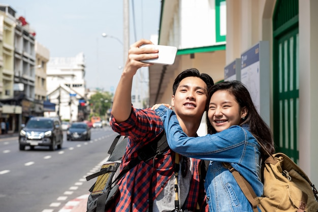 Young asian tourist couple taking selfie in bangkok city thailand