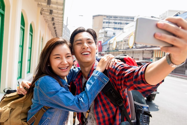 Young asian tourist girl taking selfie with boyfriend during summer vacations in bangkok city thailand