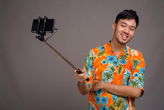 Молодой азиатский турист готов к отпуску против серого