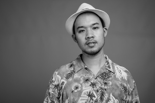 Young asian tourist man with hawaiian shirt and hat ready for vacation