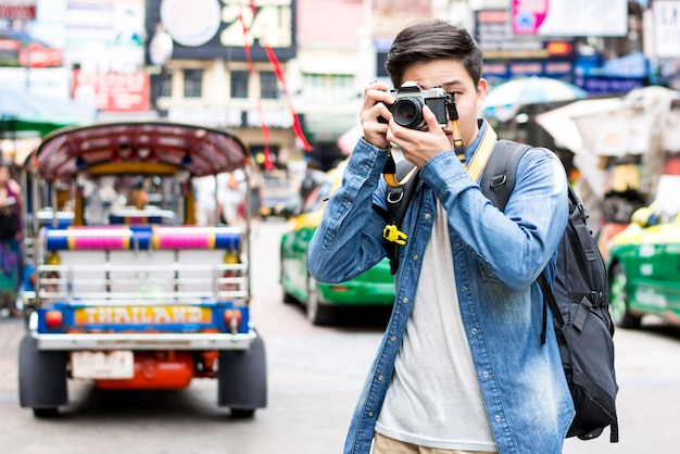 Young asian tourist photographer taking photo while traveling in bangkok