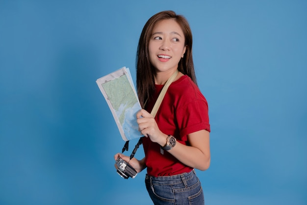 Young asian tourist smiling and holding a map and a camera on blue