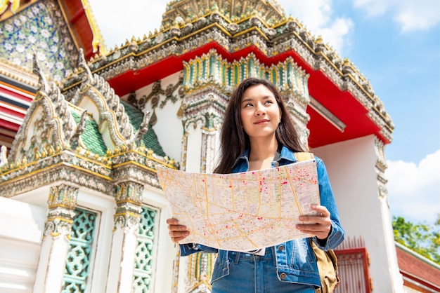 Young asian tourist woman backpacker solo traveling in ancient thai temple during summer vacations in bangkok thailand
