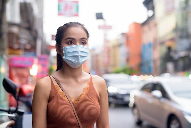 チャイナタウンでのコロナウイルスの発生と汚染からの保護のためのマスクを考えて若いアジア観光客女性
