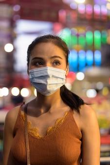 チャイナタウンの夜のコロナウイルスの発生からの保護のためのマスクと考えて若いアジア観光客女性