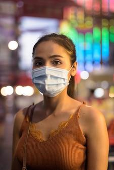 チャイナタウンの夜のコロナウイルスの発生からの保護のためのマスクを持つ若いアジア観光客女性