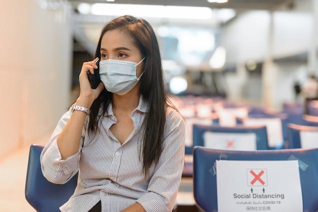 空港で距離を置いて座っている間電話で話しているマスクを持つ若いアジア観光女性