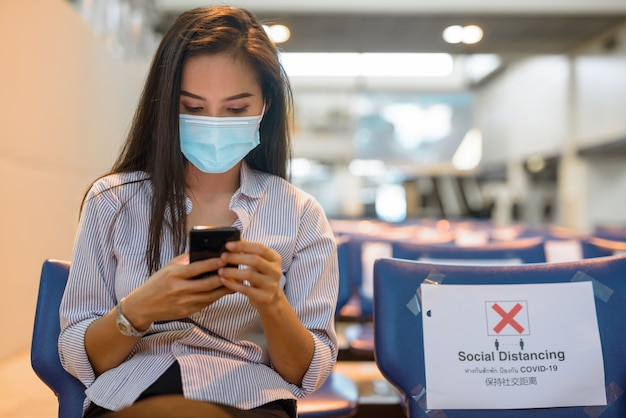 Young asian tourist woman with mask using phone while sitting with distance at the airport
