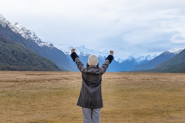 Young asian traveler celebrating success at eglinton valley, te anua, south island, new zealand