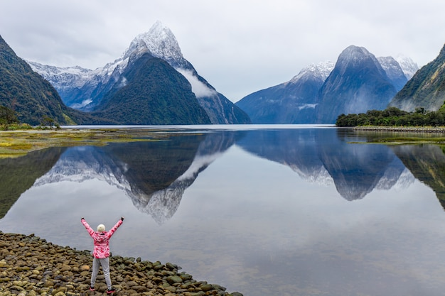 Young asian traveler celebrating success at milford sound, fiordland national park, south island, new zealand