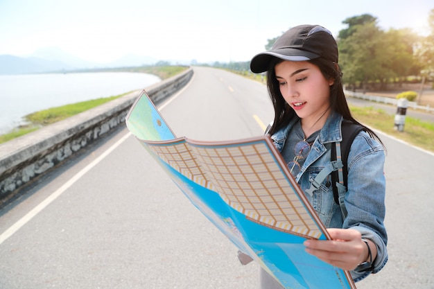 Young asian traveler searching direction on location map while traveling during holiday vacation