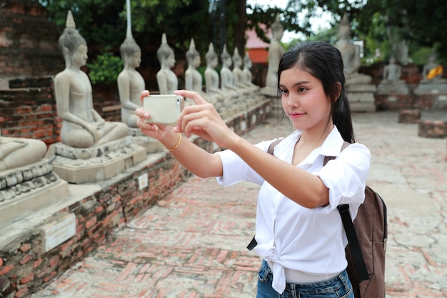 Young asian traveler using cell phone and do self portrait or taking photo in temple while traveling during holiday vacation