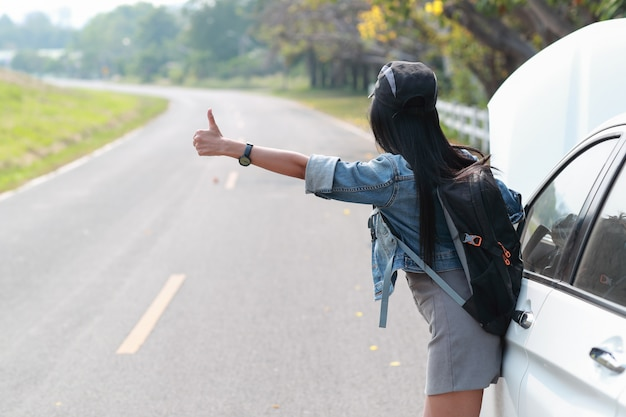 Young asian traveler with backpack and map hitchhiking on the road while traveling during holiday vacation