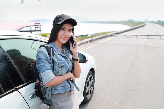 Young asian traveler with car using smart phone while traveling during holiday vacation