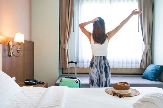 Young asian traveler woman relaxing in hotel room after check-in
