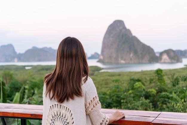 若いアジア旅行者の女性が座って、早朝、タイのパンガーのサメタナンシェ島の視点で山を見る。