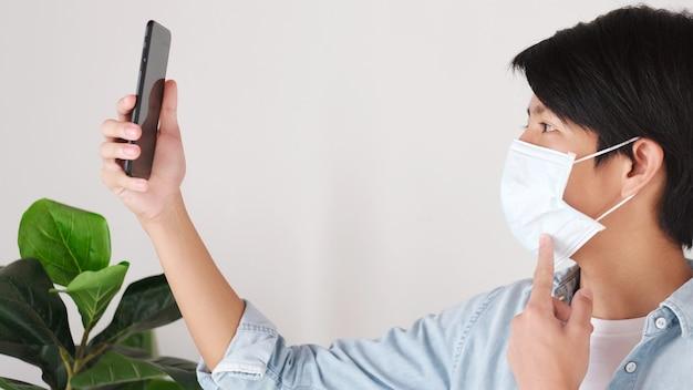 キャンパスで保護マスクを着用しながら携帯電話を持ってビデオ通話をする若いアジアの大学生、社会的距離、covid 19