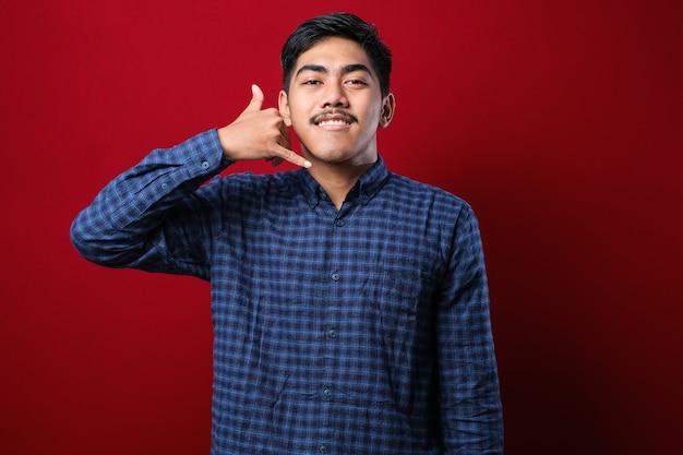 Молодой азиатский нося повседневную рубашку на красном фоне улыбается, делая телефонный жест рукой и пальцами, как разговаривает по телефону. передача концепций.