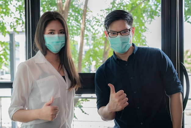 Young asian wearing face mask for protect coronavirus showing thumbs up while back to work at office