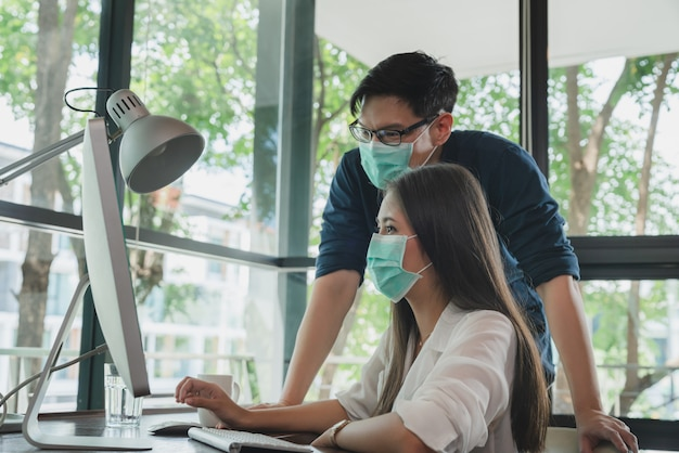 Young asian wearing face mask for protect coronavirus while working at workplace office