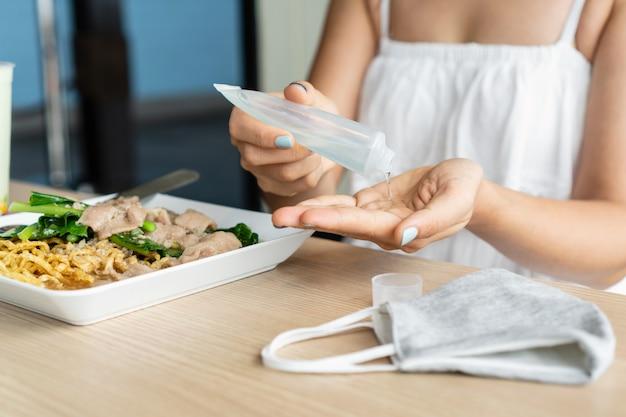 Молодая азиатская женщина прикладывая дезинфицирующее средство для рук на ее руку перед едой в ресторане для защиты от инфекционного вируса, бактерий и микробов. коронавирус covid-19, концепция здравоохранения.