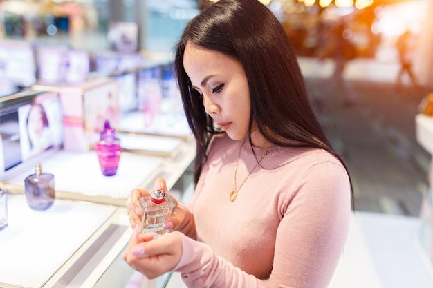 Young asian woman applying perfume on her wrist in duty free store