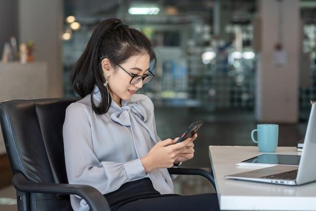 Молодые азиатские женщины счастливы сидеть по телефону за офисным столом.