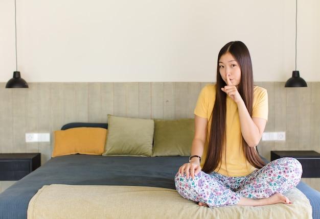 침묵과 조용함을 요구하는 젊은 아시아 여성, 입 앞에서 손가락으로 몸짓, 쉿 말 또는 비밀 유지