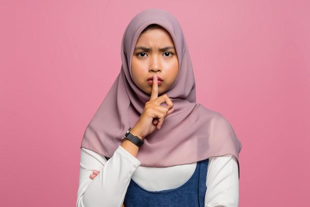 静かにすることを求める若いアジアの女性