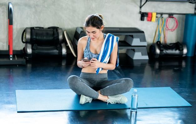 바닥 체육관에 앉아 스마트폰을 사용하는 매력적인 웃고 있는 젊은 아시아 여성