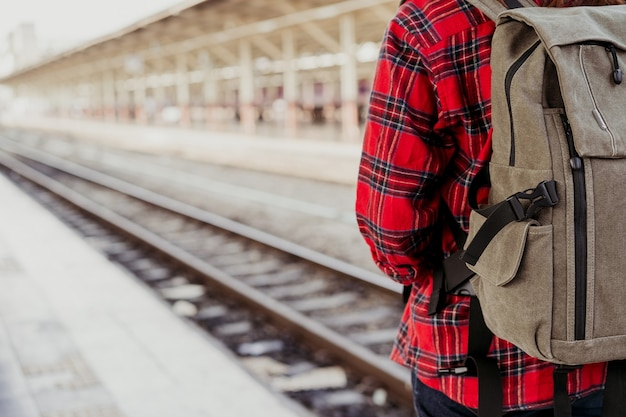 Young asian woman backpacker traveler walking alone at train station platform with backpack
