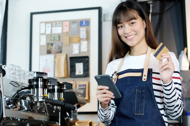 Young asian woman barista using smartphone and holding credit card