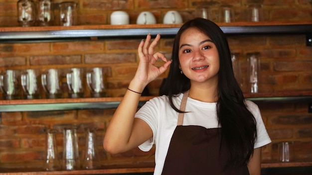 Young asian woman barista wear apron ok gesture