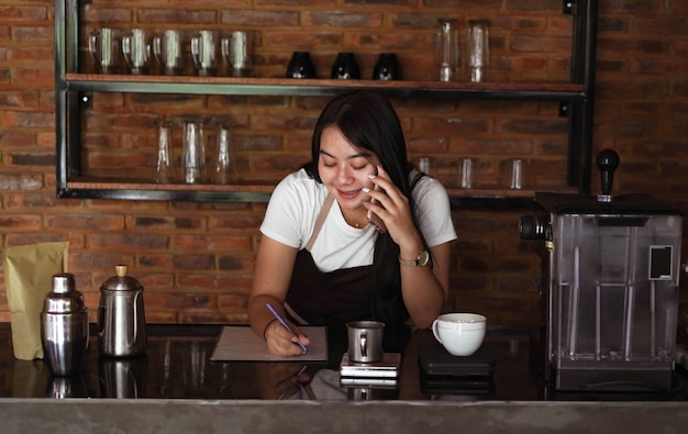 Young asian woman barista wear apron talking and receive order from customer on cellphone at coffee shop. concept of cafe store small business. female bartender writing note while listening to the client