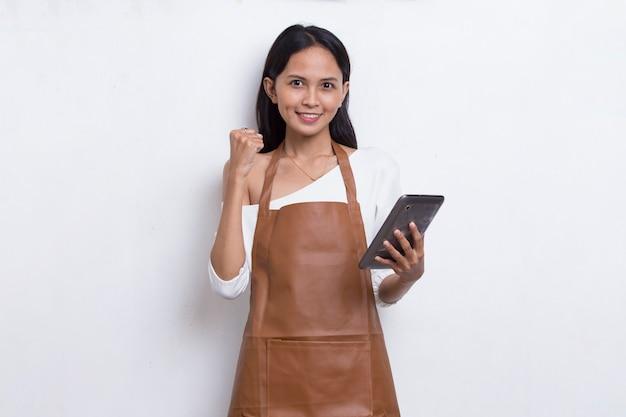 흰색 배경에 격리된 모바일 스마트폰을 사용하는 젊은 아시아 여성 바텐더 또는 웨이트리스