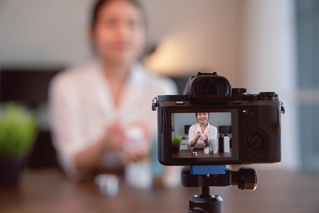 Молодое азиатское видео красоты онлайн vlogger показывает макияж на косметических продуктах и видео в реальном времени на цифровую камеру.