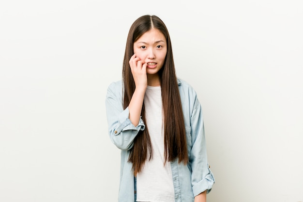 Young asian woman biting fingernails, nervous and very anxious.