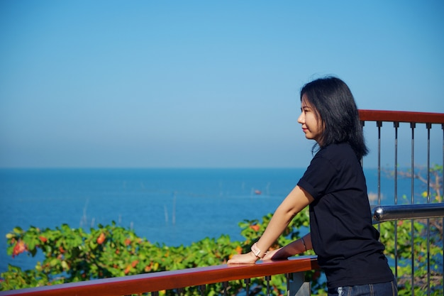 Young asian woman in black shirt standing and looking forward at sea viewpoint