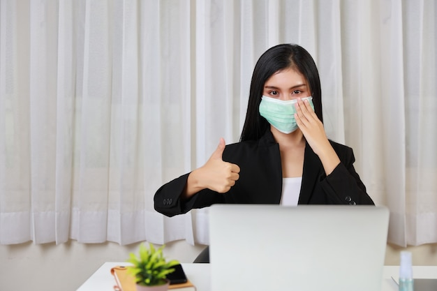 Young asian woman in black suit waring protect mask for healthcare and showing thumb up and sitting in office and working on computer laptop and smartphone