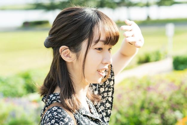 Молодая азиатская женщина блокирует яркий солнечный свет руками