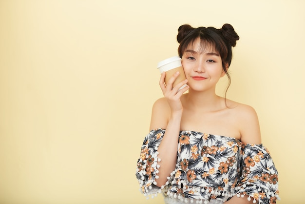 Young asian woman in blouse with bare shoulders posing and holding takeaway coffee to cheek