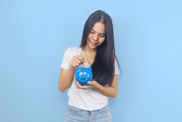 Young asian woman on blue pastel background holding piggy bank