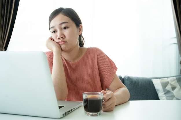 온라인 회의와 집에서 일하는 젊은 아시아 여성, 직장과 온라인 회의에 지친 여성. 의욕이 없는 프리랜서 노동자 - 아침에 집에서 일하는 지루한 아시아 소녀.
