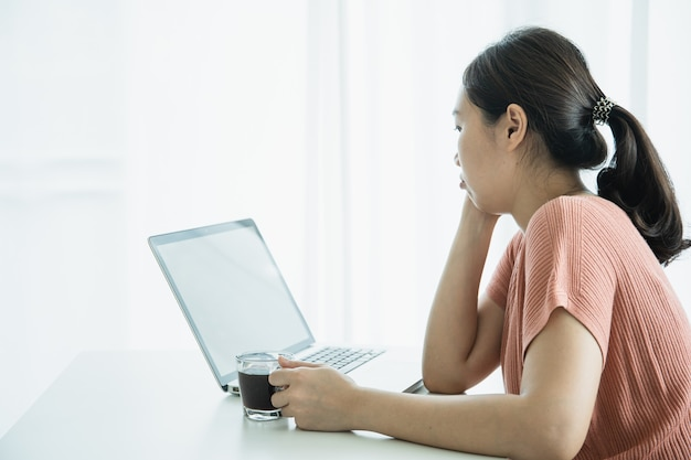 Young asian woman bored in online meeting and work from home, woman tired in her work and online meeting. unmotivated freelance worker - bored asian girl working at home in morning.