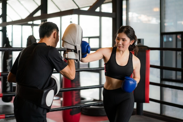 Young asian woman boxer strikes with straight punch to professional trainer in boxing stadium