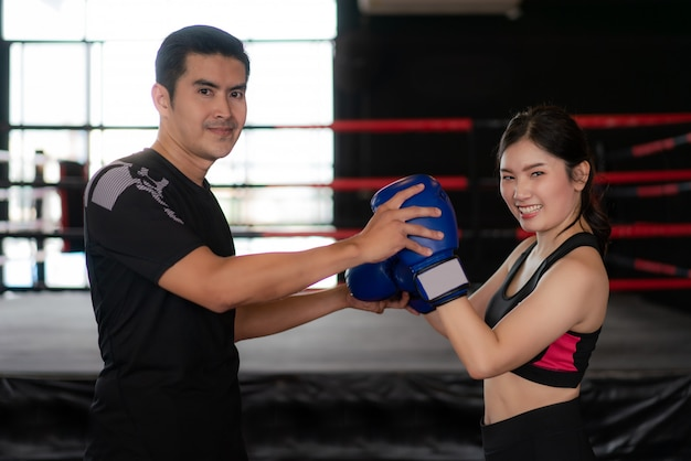Young asian woman boxer with professional trainer pose and smile at the camera during trainning.