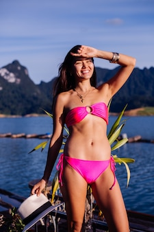 Young asian woman in bright pink bikini on vacation in thailand