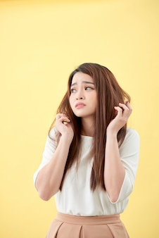 Young asian woman brushing her hair and disappointing condition her hair