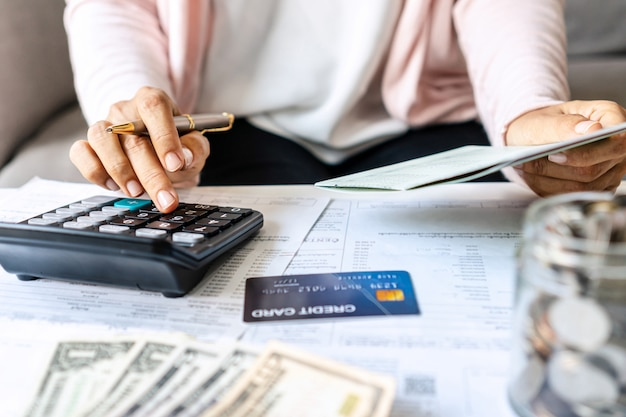 Young asian woman calculating monthy expense at her desk. home saving concept. financial and installment payment concept. close up.