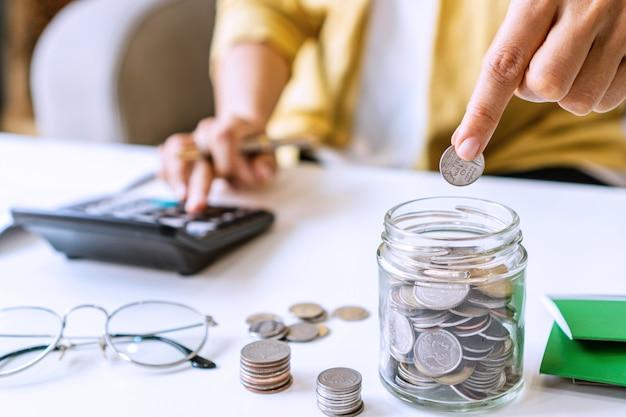 若いアジアの女性は彼女の机で毎月の収入と支出を計算します。家の節約のコンセプト。財務と分割払いのコンセプト。閉じる。